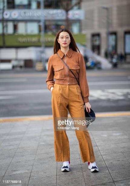 A guest is seen wearing brown zipped jacket mustard pants at the Hera Seoul Fashion Week 2019 F/W at Dongdaemun Design Plaza at Dongdaemun Design...