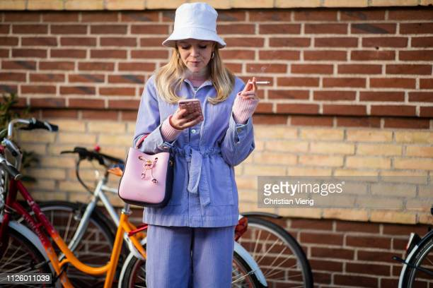 A guest is seen wearing bucket hat belted purple jacket outside Blanche during the Copenhagen Fashion Week Autumn/Winter 2019 Day 1 on January 29...