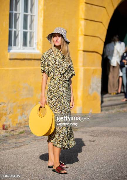 Guest is seen wearing bucket hat, dress with print, yellow bag outside Stine Goya during Copenhagen Fashion Week Spring/Summer 2020 on August 08,...