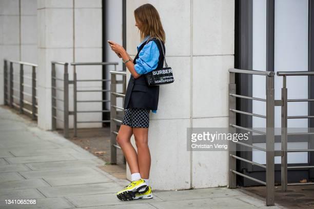 Guest is seen wearing Burberry bag outside Nensi Dojaka during London Fashion Week September 2021 on September 17, 2021 in London, England.