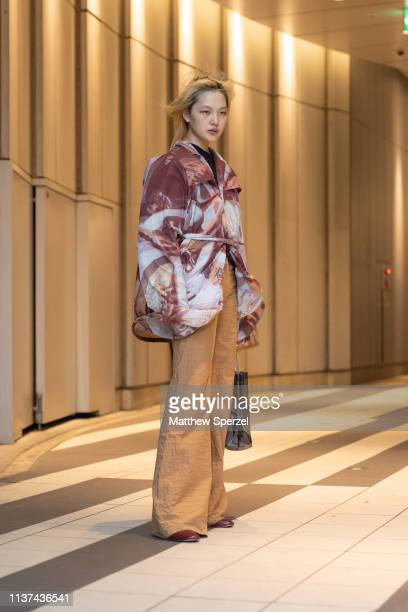 A guest is seen wearing burgundy/white design jacket gold pants during the Amazon Fashion Week TOKYO 2019 A/W on March 21 2019 in Tokyo Japan