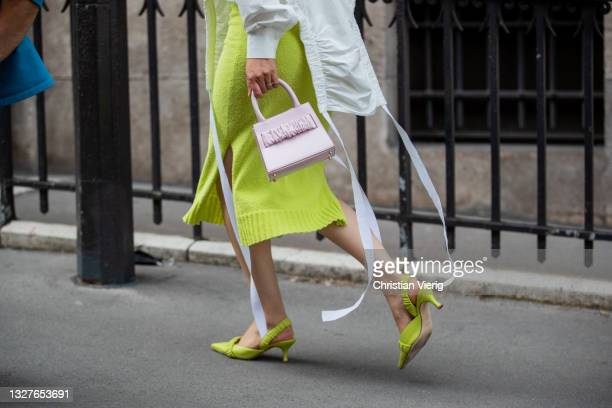 Guest is seen wearing button shirt, yellow skirt, pink bag outside Zuhair Murad on July 07, 2021 in Paris, France.