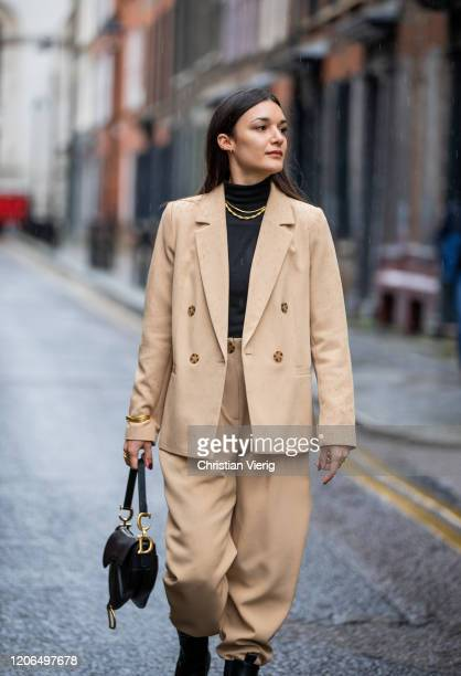 Guest is seen wearing camel suit, black Dior bag outside Toga during London Fashion Week February 2020 on February 15, 2020 in London, England.