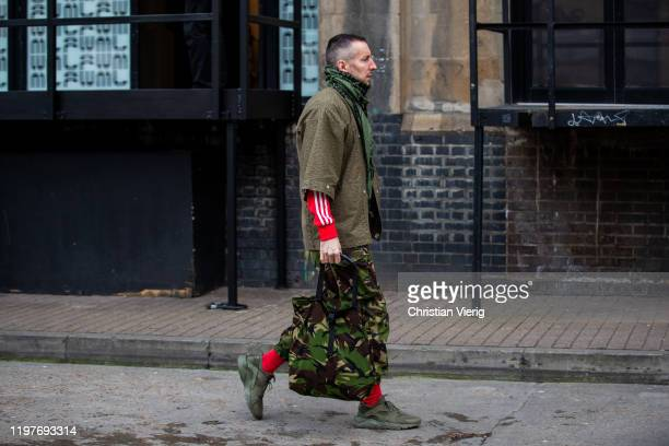 A guest is seen wearing camouflage pants bag during London Fashion Week Men's January 2020 on January 05 2020 in London England