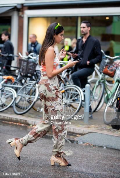 A guest is seen wearing camouflage pants outside Saks Potts during Copenhagen Fashion Week Spring/Summer 2020 on August 08 2019 in Copenhagen Denmark