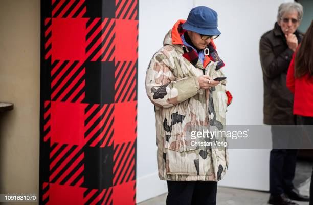 A guest is seen wearing camouflage parka blue bucket hat during the 95th Pitti Uomo at Fortezza Da Basso on January 09 2019 in Florence Italy