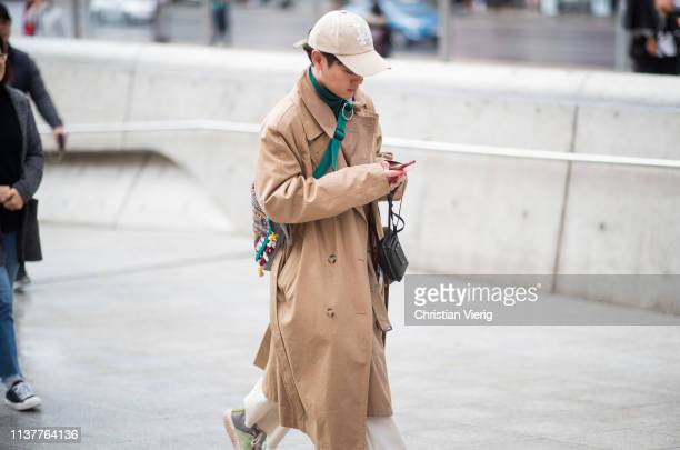 A guest is seen wearing cap brown trench coat at the Hera Seoul Fashion Week 2019 F/W at Dongdaemun Design Plaza at Dongdaemun Design Plaza on March...