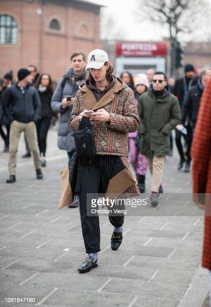 A guest is seen wearing cap Prada belt bag ripped off coat with print during the 95th Pitti Uomo at Fortezza Da Basso on January 09 2019 in Florence...