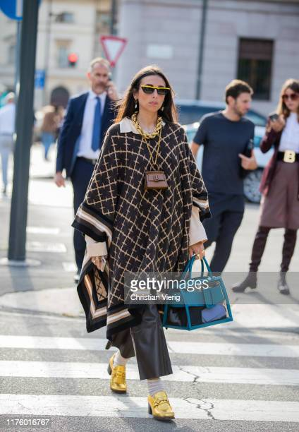 Guest is seen wearing cape, brown mini bag outside the Tod's show during Milan Fashion Week Spring/Summer 2020 on September 20, 2019 in Milan, Italy.