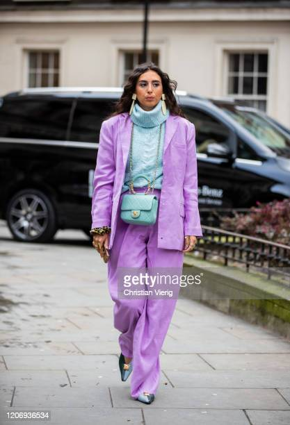 A guest is seen wearing Chanel bag turquoise turtleneck knit pink blazer and wide leg pants outside Erdem during London Fashion Week February 2020 on...