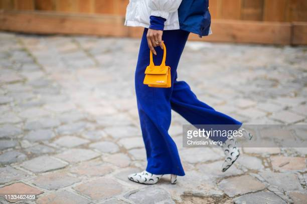 A guest is seen wearing Chanel jacket blue pants yellow mini Jacquemus bag outside Thom Browne during Paris Fashion Week Womenswear Fall/Winter...