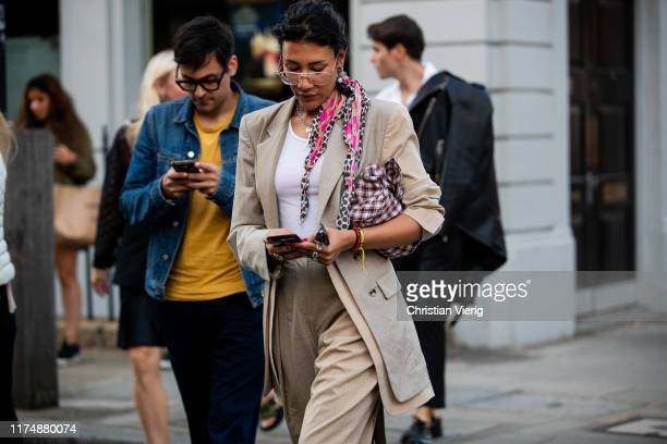 A guest is seen wearing checkered bag beige blazer scarf outside Rejina Pyo during London Fashion Week September 2019 on September 14 2019 in London...