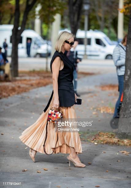 Guest is seen wearing Chloe bag, pleated skirt, black sleeveless vest outside Elie Saab during Paris Fashion Week Womenswear Spring Summer 2020 on...