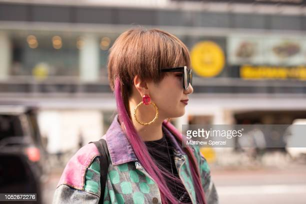 A guest is seen wearing coloful handpainted denim jacket blue jeans black shirt and tote bag during the Amazon Fashion Week TOKYO 2019 S/S on October...