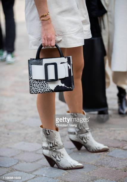 A guest is seen wearing cowboy boots with snake print two tone Boyy bag outside Designers Remix during Copenhagen Fashion Week Spring/Summer 2020 on...