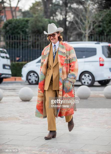 A guest is seen wearing cowboy hat brown suit Ralph Lauren coat with graphic print during Pitti Uomo 97 at Fortezza Da Basso on January 07 2020 in...