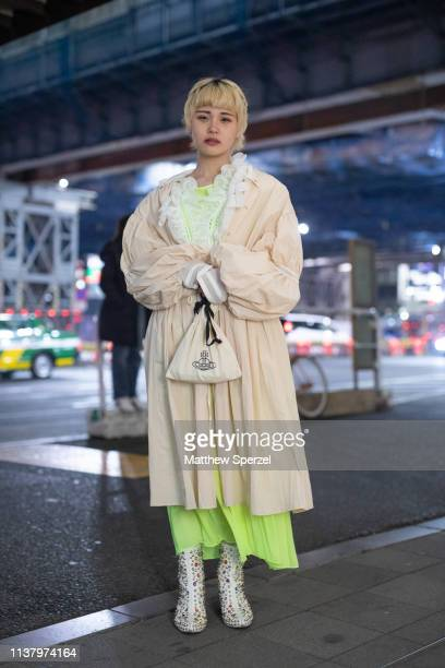 A guest is seen wearing cream coat neon green dress during the Amazon Fashion Week TOKYO 2019 A/W on March 23 2019 in Tokyo Japan