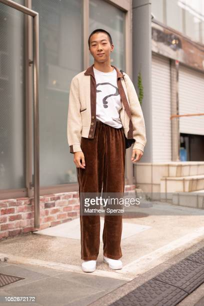 A guest is seen wearing cream jacket golden brown velvet trousers white question mark shirt and white sneakers during the Amazon Fashion Week TOKYO...