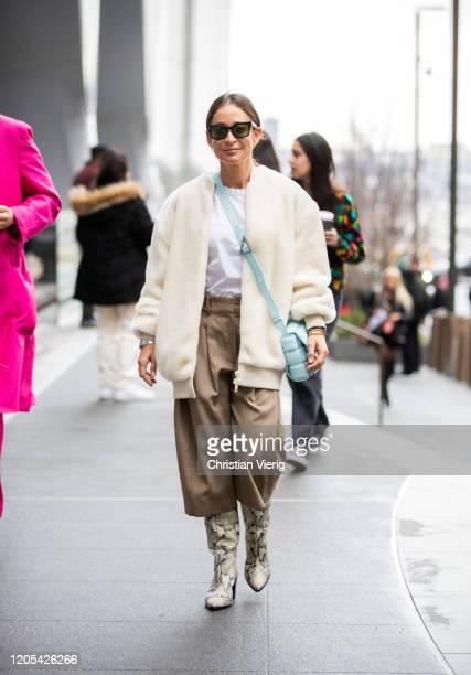 Guest is seen wearing creme white jacket, Bottega bag, brown pants outside Carolina Herrera during New York Fashion Week Fall / Winter on February...
