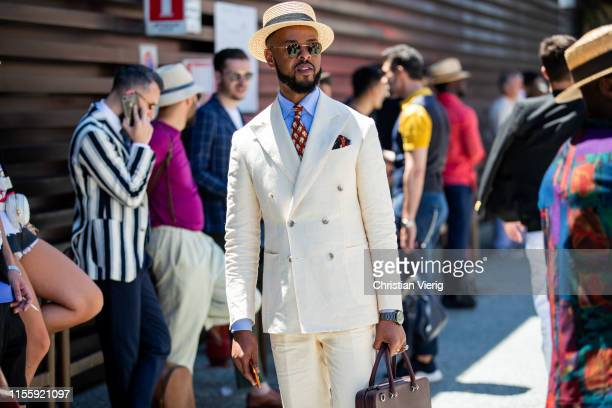 A guest is seen wearing creme white suit during Pitti Immagine Uomo 96 on June 13 2019 in Florence Italy