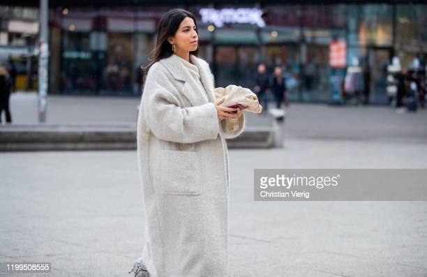Guest is seen wearing creme white wool coat, boots with snake print, beige Bottega Veneta Pouch bag during the Berlin Fashion Week Autumn/Winter 2020...