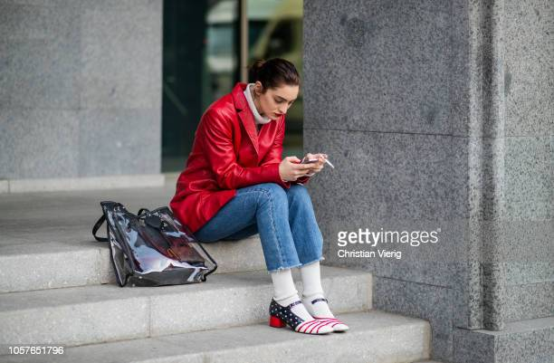 A guest is seen wearing cropped denim jeans white socks red leather jacket shoes with America flat print see trough bag during MercedesBenz Tbilisi...