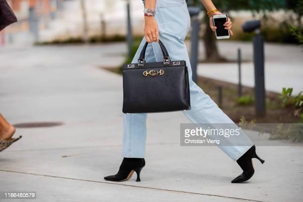 Guest is seen wearing denim jeans, black bag outside Brøgger during Copenhagen Fashion Week Spring/Summer 2020 on August 06, 2019 in Copenhagen,...