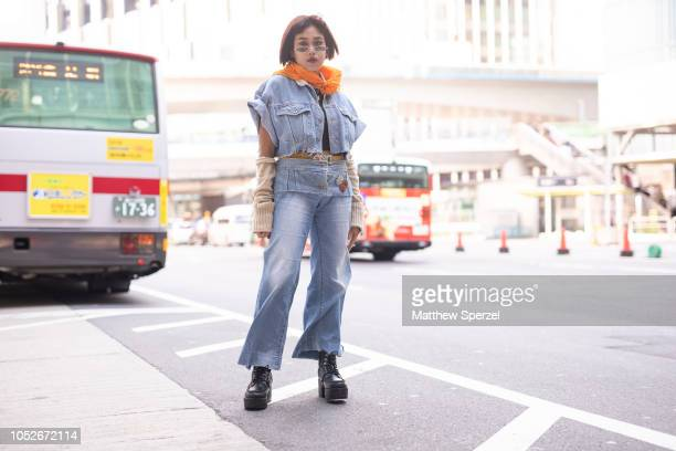 A guest is seen wearing denim outfit with arm warmers black boots and orange scarf during the Amazon Fashion Week TOKYO 2019 S/S on October 20 2018...