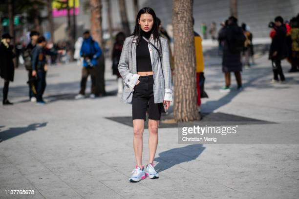A guest is seen wearing denim shirts grey blazer cropped top at the Hera Seoul Fashion Week 2019 F/W at Dongdaemun Design Plaza at Dongdaemun Design...