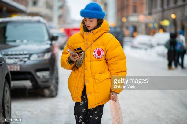 Guest is seen wearing Dior saddle bag, yellow puffer down feather coat Acne, blue beanie, flared cropped pants, white boots outside Ida Sjöstedt...