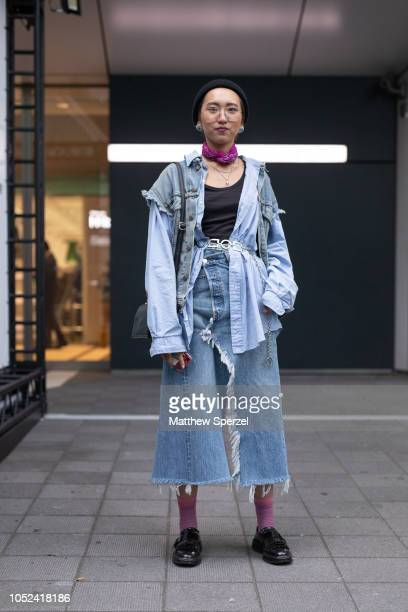 A guest is seen wearing distressed denim jeans and vest with blue shirt purple scarf and black beanie during the Amazon Fashion Week TOKYO 2019 S/S...