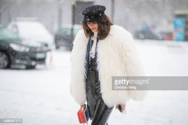 A guest is seen wearing flat cap black vinyl overall creme white fake fur jacket Chanel bag outside Chanel during Haute Couture Spring Summer 2019...