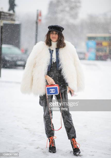 A guest is seen wearing flat cap black vinyl overall creme white fake fur jacket boots Chanel bag outside Chanel during Haute Couture Spring Summer...