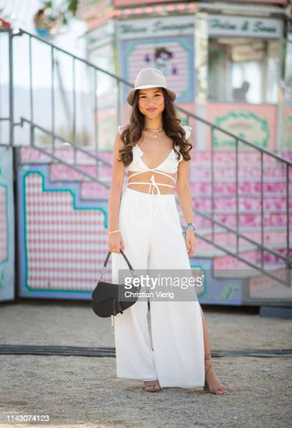 Guest is seen wearing flat hat, white cropped top, wide leg pants at the Revolve Festival during Coachella Festival on April 14, 2019 in La Quinta,...