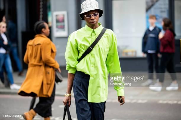 Guest is seen wearing floppy hat with snake print, neon jacket outside John Lawrence Sullivan during London Fashion Week Men's June 2019 on June 08,...