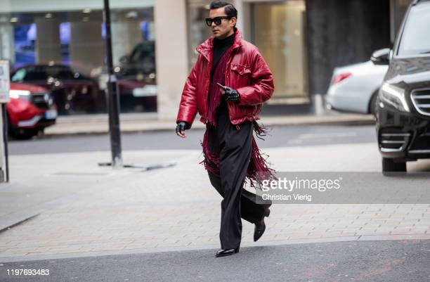 A guest is seen wearing gloves boredeaux red pants outside Chalayan during London Fashion Week Men's January 2020 on January 05 2020 in London England