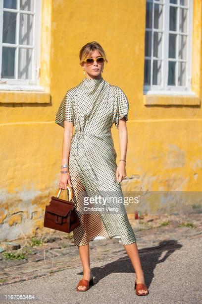 Guest is seen wearing golden dress outside Stine Goya during Copenhagen Fashion Week Spring/Summer 2020 on August 08, 2019 in Copenhagen, Denmark.
