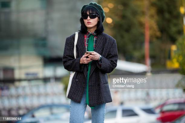 Guest is seen wearing green beret, plaid jacket, denim jeans, green scarf during day 3 of the Mercedes-Benz Tbilisi Fashion Week on November 02, 2019...
