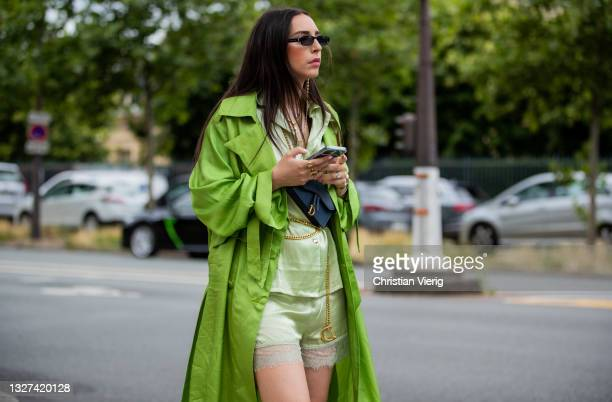 Guest is seen wearing green coat, Dior bag in blueoutside Dior on July 05, 2021 in Paris, France.