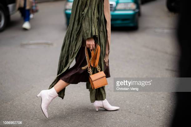 A guest is seen wearing green coat with slits brown bag white ankle boots during MercedesBenz Tbilisi Fashion Week on November 3 2018 in Tbilisi...