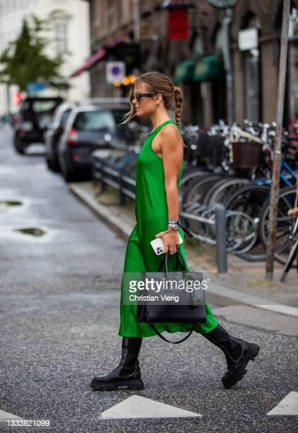 Guest is seen wearing green dress, Saint Laurent bag outside The Garment on August 10, 2021 in Copenhagen, Denmark.