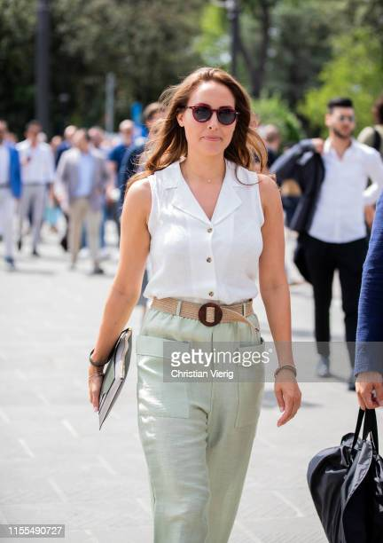 A guest is seen wearing green pants white blouse during Pitti Immagine Uomo 96 on June 12 2019 in Florence Italy