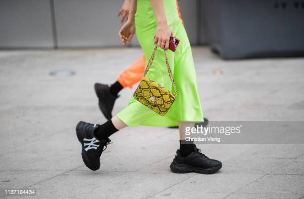 A guest is seen wearing green skirt bag with snake print black sneaker at the Hera Seoul Fashion Week 2019 F/W at Dongdaemun Design Plaza at...