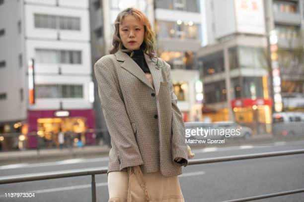 A guest is seen wearing grey blazer black turtleneck cream layered skirt and cream bag with black boots during the Amazon Fashion Week TOKYO 2019 A/W...