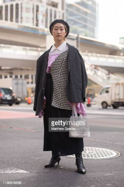 A guest is seen wearing grey blazer checker wrap pink shirt white collared shirt and black skirt and boots during the Amazon Fashion Week TOKYO 2019...