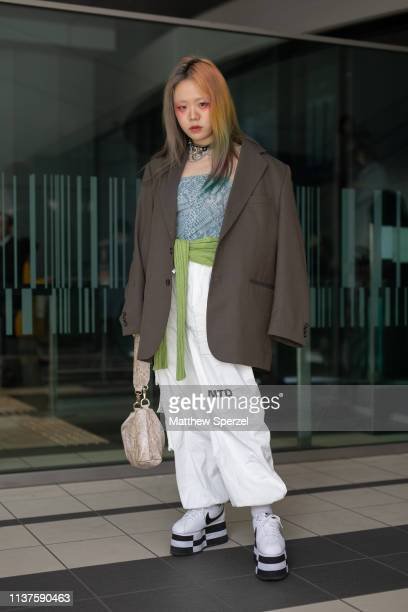 A guest is seen wearing grey blazer oversized blue top green sash belt white pants and Nike platform sneakers with taupe bag during the Amazon...