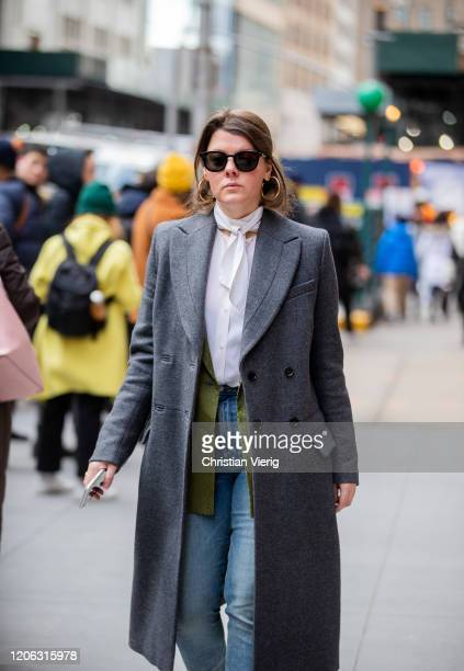 A guest is seen wearing grey coat denim jeans white blouse outside Michael Kors during New York Fashion Week Fall / Winter 2020 on February 12 2020...