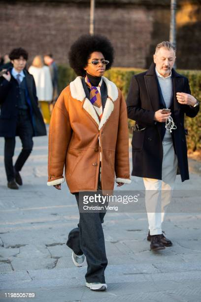 A guest is seen wearing grey pants brown shearling coat during Pitti Uomo 97 at Fortezza Da Basso on January 09 2020 in Florence Italy