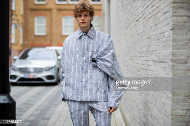 A guest is seen wearing grey striped jacket and pants outside Chalayan during London Fashion Week Men's January 2020 on January 05 2020 in London...