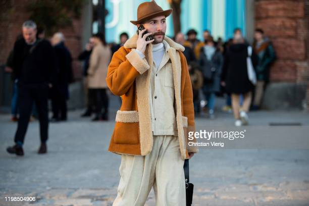 A guest is seen wearing hat and shearling jacket during Pitti Uomo 97 at Fortezza Da Basso on January 09 2020 in Florence Italy